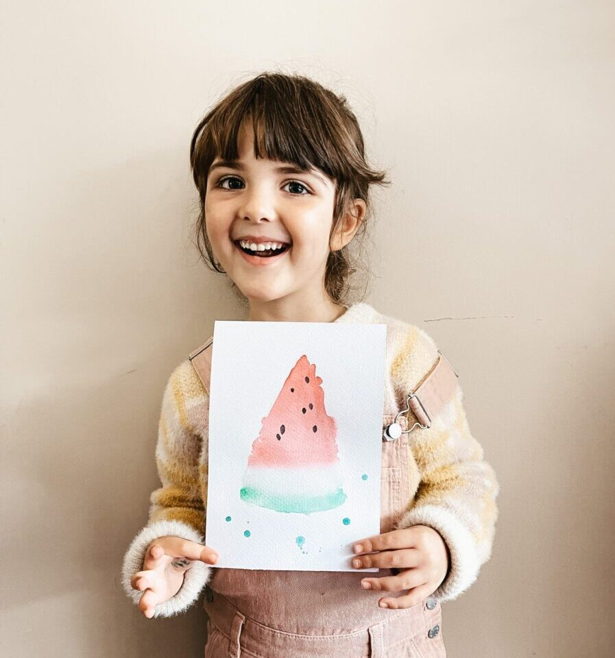 child holding watercolour painting